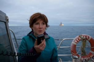 Niamh O'Flynn, Oil Free Otago Spokesperson, sends a message to the drill ship the Noble Bob Douglas explaining her opposition to deep sea drilling. The Oil Free Otago flotilla is a coalition of Otago residents who oppose deep sea drilling off our coast. Photo by Nick Tapp - nicktappvideo.com
